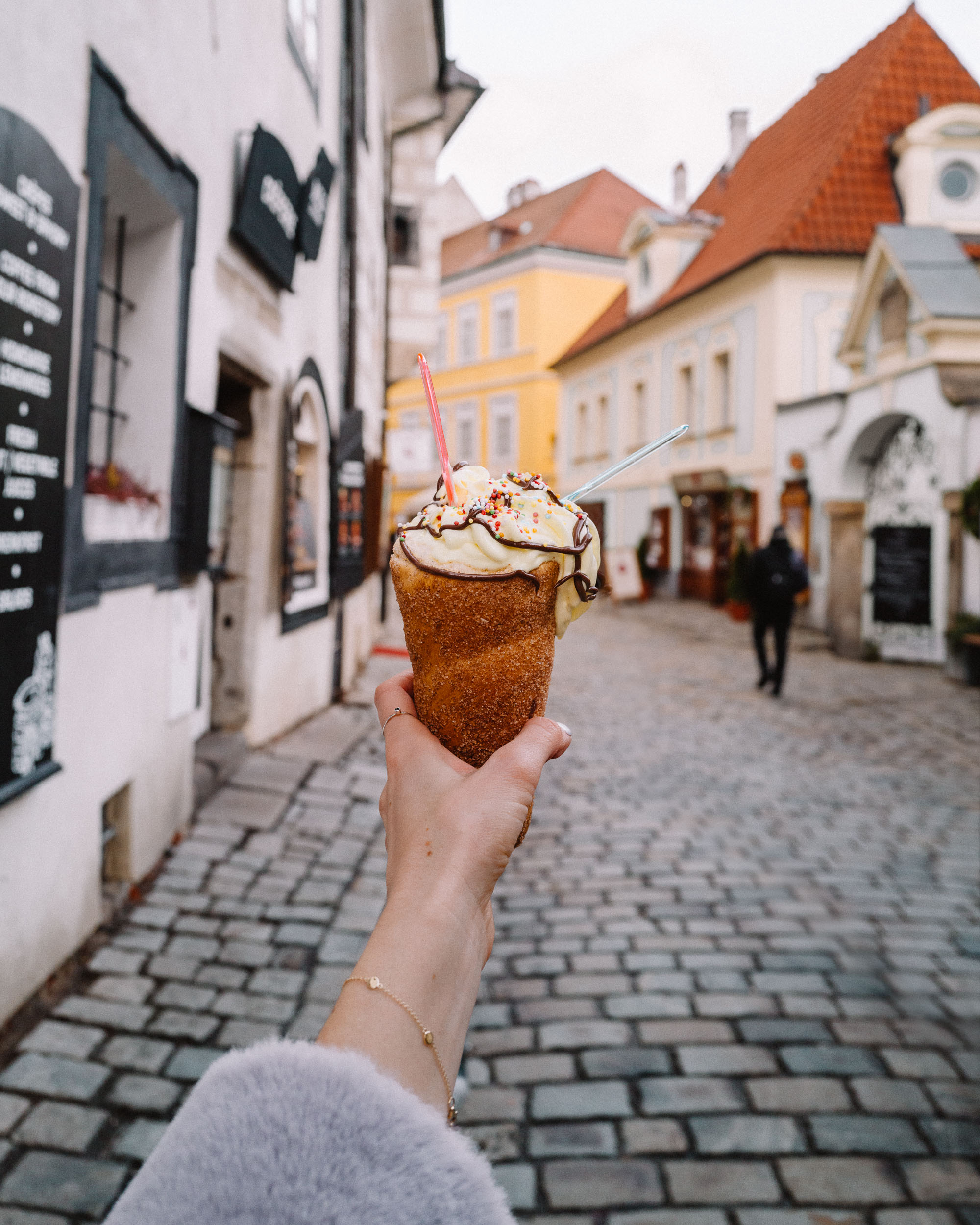 Woman's hand holding a chimney cake in Cesky, Krumlov.