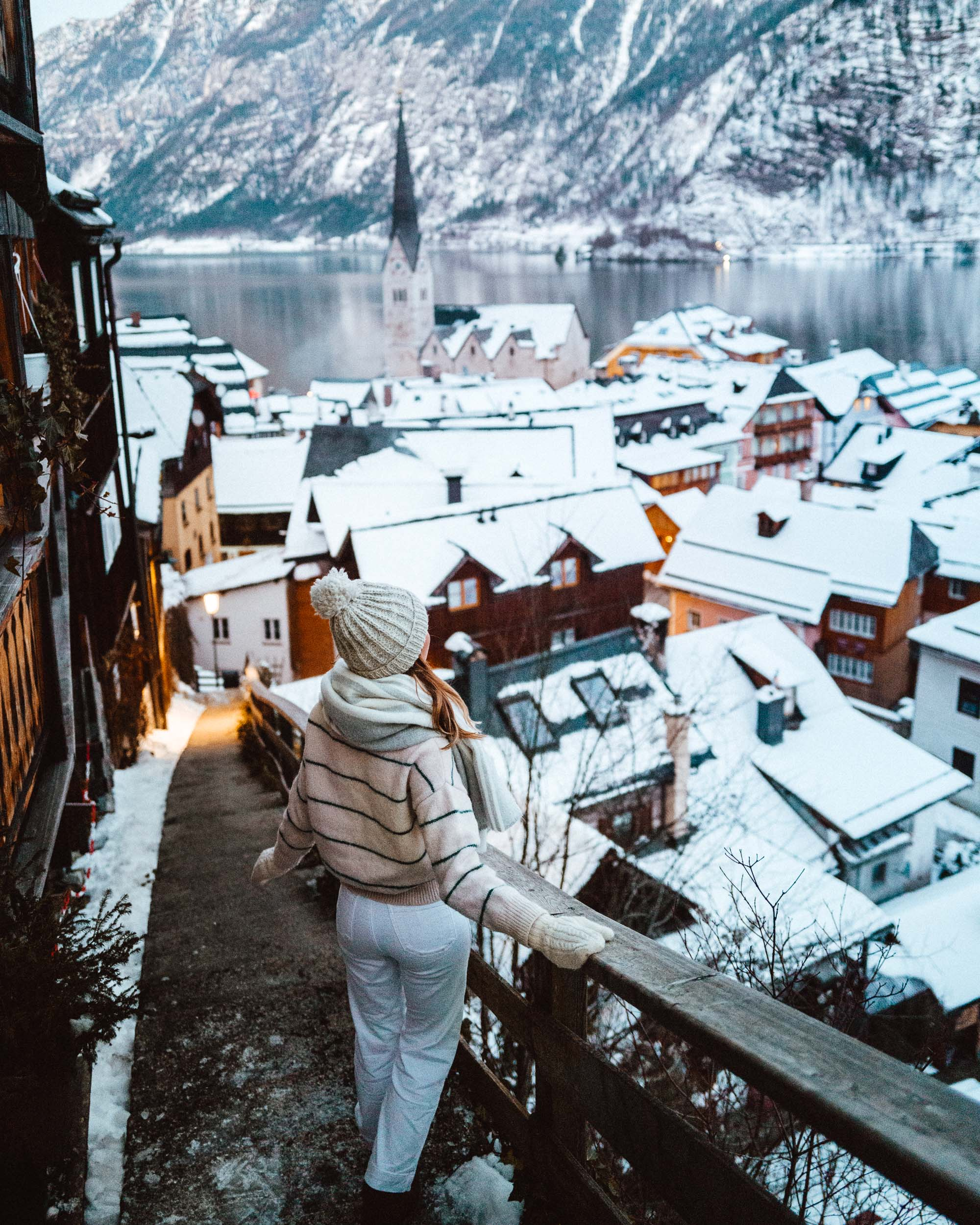Staircase with view of Hallstatt Austria rooftops in wintertime with snow and church in the background